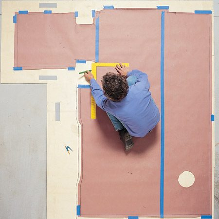 <b>Photo 8: Mark the underlayment</b></br> Transfer the shape of the bathroom floor to the underlayment by aligning the blade of the framing square with the reference line and drawing a line along the outside edge. Transfer the curved portions with the compass. Use a circular saw and jigsaw to cut out the plywood.