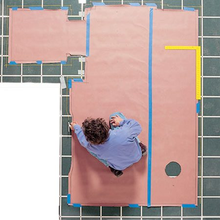 <b>Photo 11: Place the template on the flooring</b></br> Unroll the vinyl flooring on a clean surface and tap the template to it. If the flooring has a pattern in it, align the template for the most desirable layout. Tape the template to the vinyl flooring and transfer the marks with the framing square and compass.