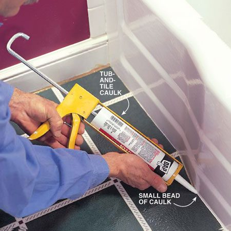 <b>Photo 16: Apply caulk</b></br> Replace the toilet and reinstall the moldings. Caulk along the bathtub and around the toilet with silicone or latex tub-and-tile caulk.