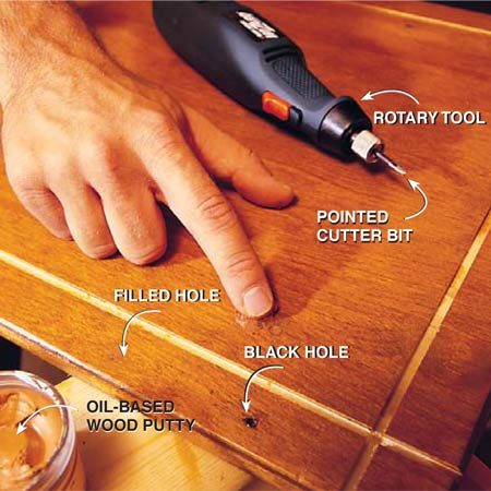 <b>Photo 4: Fill holes</b><br/><p>Fill the old hardware holes in the doors, drawers and cabinet frames after the final coat of finish is dry. To match the color exactly, mix two or more shades of oil-based wood putty. After filling the holes, spot-finish the putty with shellac (water-based polyurethane won&#39;t stick to the putty). For blackened holes like the one shown, use a rotary tool with a pointed cutter bit to dig out the black areas before filling.</p>  <p><strong>Tip:</strong> If you need to sand the grooves, wrap a piece of sandpaper around a paint stirrer stick and run it down the grooves a few times.</p>