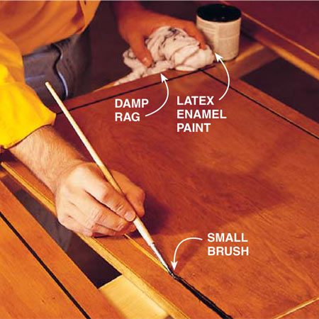 <b>Photo 5: Paint accent lines</b></br> Paint your door grooves with a complementary color in latex enamel paint. Match color from hardware, countertops or appliances. Keep a damp rag at hand to wipe away mistakes. It will take two coats for complete coverage.
