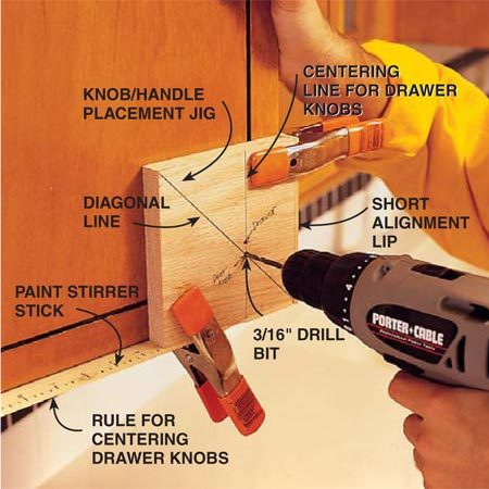 <b>Photo 8: Drill holes for handles</b><br/>Use a homemade jig to  accurately and uniformly place the knobs or handles on the doors and drawers. Make it from a 6 x 6 x 3/4-in. block of wood and two thin straight boards (one short and one long) about 1-1/8 in. wide (paint stirrer sticks work well) screwed to the sides of the block. On the long lip (12 in.), mark a rule, starting at the center line for drawer knobs. To use the rule, you&#39;ll have to divide the width of a particular drawer in half. To use the jig on a drawer face, remove the short lip from the block. Use two heavy-duty spring clamps to hold the jig in place.