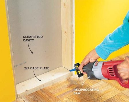 <b>Photo 1: Open the wall</b></br> Open the wall for the chute by carefully removing the baseboard then using a utility knife to cut out a chunk of drywall 42 in. high down the center of each stud. Use a reciprocating saw or handsaw to cut out the base plate between the studs. Work the plate out carefully; the drywall and the trim on the opposite side might be nailed to it. Then cut a hole through the plywood floor for the duct to slide through. At the top of the cutout, install a 2x4 piece of blocking between the studs as a nailing surface for the frame of the laundry door.