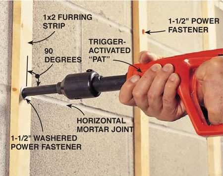 <b>Fire the fasteners into the mortar joints</b></br> Attach furring strips to walls using either 1-1/2 in. standard drive pins or washered drive pins (if the wood splits). The trigger-activated PAT shown is a single-shot tool that loads like the hammer-activated model. For the best bond, use adhesive on the 1x2s first and fire the drive pins only into horizontal mortar joints. There may not be enough mortar in the vertical joints to properly capture a fastener. If you must fasten into the concrete block face, fire only into the core wall located at the very center of the block or you may crack the block.