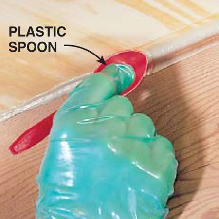 <b>Smooth the bead</b></br> Push the bead of polyurethane construction adhesive deeper into the flooring gap with a plastic spoon instead of your finger. This adhesive is extremely sticky. Wear gloves when handling it and expect that any tools you use to work the adhesive will have to be cleaned with paint thinner, or in the case of the spoon, just thrown away.