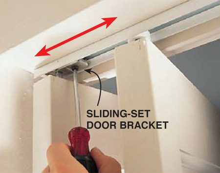<b>Photo 1: Top bracket</b></br> Loosen the set screw on the top bracket and slide the bracket slightly along the track to adjust the space between the top of the doors. Then retighten the screw, close the doors and check the fit. Adjust both doors.