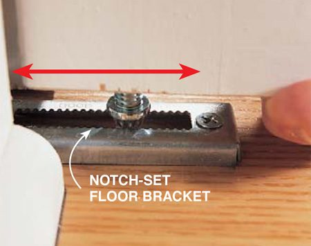 <b>Photo 2: Floor bracket</b></br> Move the pin in each bottom floor bracket to adjust the vertical gap and the space between the bottom of the doors and the floor. There are two types of bottom brackets. One requires you to loosen a set screw and slide the bracket in or out. The style shown in the photo requires you to lift the door and drop the pin into a different notch in the bracket.