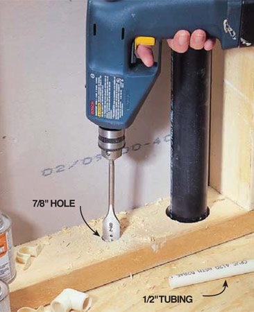 <b>Photo 9: Bore slightly over-sized holes</b><br/>Bore 7/8-in. or larger holes for 1/2-in. tubing and 1-in. or larger holes for 3/4-in. tubing. If the edge of the hole is closer than 1 in. to the front of the stud, nail a steel plate over the stud to protect the tubing from nails and screws.