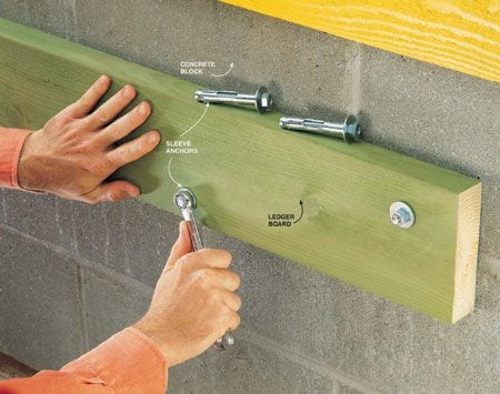 <b>Photo 7: Insert anchor into predrilled hole</b></br> Drill 1/2-in. holes, insert the anchors and tighten the nuts to fasten a 2x6 ledger board to concrete block.