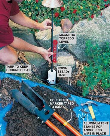 <b>Photo 5: Make sure the fixtures are straight</b></br> Install the path light by digging a hole deep enough so the top of the PVC footing is level with the ground surface. Use a torpedo level to level the light pole and pack soil around the base. Use aluminum tent stakes to secure the unburied wire in the bedding areas, then cover it with mulch.
