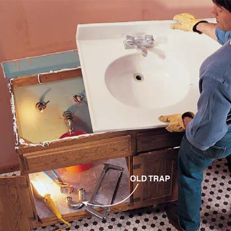 <b>Photo 1: Disconnect the pipes and remove the old sink</b></br> Shut off the water at the main shutoff valve. Remove the trap by unscrewing the slip nuts and pulling it down. Cut the tubes that supply water to the faucet with a hacksaw or tubing cutter or loosen the nuts and pull them out. Lift off the vanity top and remove the vanity cabinet.