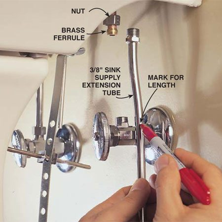<b>Photo 16: Cut the supply tubes</b></br> Mark the supply tubes and cut them with a tubing cutter. Bend them to fit and connect them to the valve and faucet with the nut and brass ferrule provided.