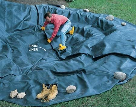 <b>Photo 5: Spread the rubber liner</b></br> Lay in the liner so it loosely conforms to the contours of the hole. Don't worry about folds and ripples; they'll flatten out when you add water. Put rocks on one side to hold the liner in place while you adjust the other. Any excess material can be trimmed off with scissors or a utility knife after the pond is full of water and encircled with rocks.
