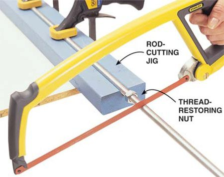 <b>Photo 10: Cut the rod</b><br/>Saw the 1/2-in. threaded rod with a hacksaw. You can clamp the threaded rod in a vise as you cut it; just don't mar the threads within 2 in. of each end. If you don't have a vise, you can support the rod with a 2x4 block with a groove cut in it and some soft-grip clamps as shown. Always thread a standard nut onto the threads beyond the cutoff. Remove the nut after the cut to help restore the threads.