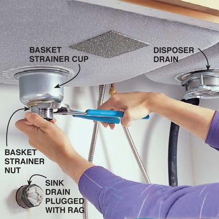 <b>Photo 5: Attach the undersink connections</b></br> Assemble the undersink half of the basket strainer assembly and tighten the large nut with the slip-joint pliers. Hold the basket with your hand to keep it from spinning. Reassemble the disposer drain and tighten the three screws. Clean the excess plumber's putty from around the drain openings and polish the sink with a dry cloth.