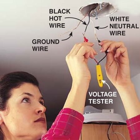 <b>Photo 8: Remove the old light fixture</b></br> Test for live wires. Switch off the circuit breaker or remove the fuse at the main electrical panel to shut off the power to the light. Then remove the screws that hold the old light fixture, pull it down and disconnect the wires. Double-check that the electricity is off by placing the two leads of a voltage tester between every possible pair of wires. If the tester lights up, the power is still on. Do not continue until you find and turn off the correct circuit breaker.