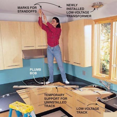 <b>Photo 10: Bend the track</b></br> <p>Bend the track to the desired shape. Follow the instructions included with the track system. Support the track on the countertop directly under its eventual position on the ceiling. Mark the standoff locations no more than 4 ft. apart and wherever two track sections are joined. Then use a string and plumb bob to transfer these locations to the ceiling. Attach a standoff at each location with the mounting hardware provided.</p>  <p><strong>Note:</strong> Position the track far enough from cabinets so open doors don't hit the light fixtures. </p>