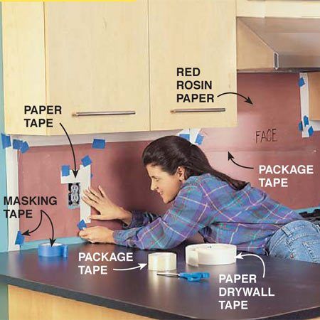 """<b>Photo 13: Make a backsplash template</b></br> Make a paper template. Switch off the circuit breakers or remove the fuses at the main panel to disconnect the power to all the switches and receptacles in the backsplash area. Take rough measurements of the backsplash area. Then cut kraft or red rosin paper about 2 in. smaller than the area you intend to cover and tape it to the wall with small pieces of masking tape, leaving about an inch of wall showing all around. Cut around the outer edge of the outlet and switch boxes. Secure strips of paper drywall tape to the pattern paper to establish precise edges. Mark the """"face"""" of each template, that is, the side that shows."""