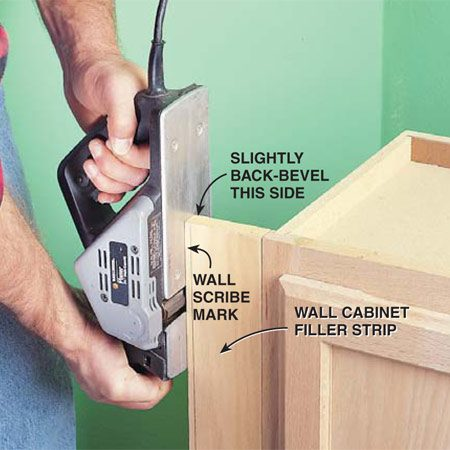 "<b>Photo 5: Plane filler boards for tight fitting cabinets</b></br> Taper-cut filler boards so cabinets fit tightly against walls. Ensure this no-gap fit by carefully shaving to the wall scribe mark and angling the planer slightly to cut more wood off the backside of the board than is cut off the front. This is called ""back beveling."" Plane the entire edge of the filler board by raising the cabinet high enough off the floor to allow the tool to complete its pass."