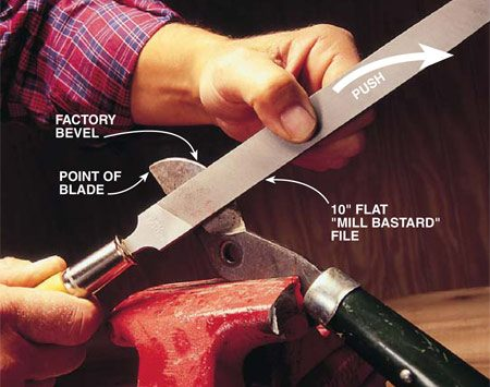 <b>Photo 4: File along the factory bevel.</b></br> File the edge of the pruning blade using two hands. Start at the point and follow the curve of the factory bevel. Make one complete stroke from the point to the base of the blade. Apply light pressure in a direction away from you. Examine the edge after each stroke of the file to ensure you're following the path of the factory bevel. Once you've exposed fresh steel along a consistent curve, feel the back side for burrs. Sand the burrs away using the technique described in Photo 3.