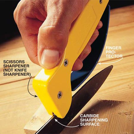 <b>Photo 6: Pull the sharpener along the blade</b></br> If tightening the pivot nut and oiling the clippers failed to make your grass clippers cut better, remove the pivot nut. Separate the blades. Hold one of the blades on a wood block with the cutting edge up. Pull the scissors sharpener firmly from the base of the blade to the point. Be sure the carbide sharpening edge makes full contact with the factory bevel of the blade. This bevel is slight, not at all like that of a kitchen knife. Pull the scissors sharpener across the blade until the blade is sharp. Usually it takes about 10 passes. When you're finished with the first blade, do the same with the next.