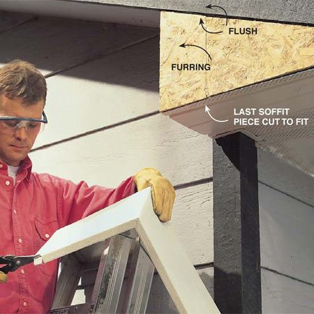 <b>Photo 9: Cut to fit</b></br> Hold the fascia piece in place to mark notches around house trim. Then cut them with tin snips.