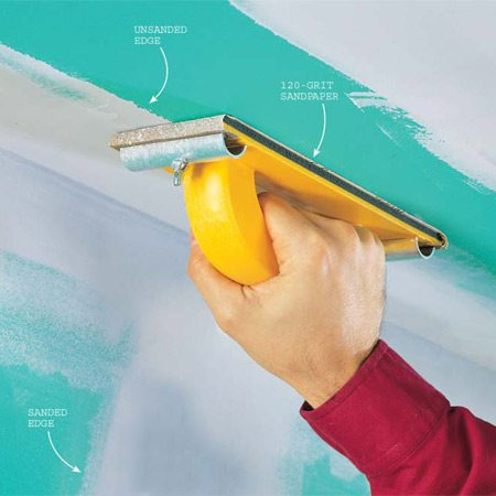 <b>Photo 16: Sand the compound lightly </b></br> Sand with a block and 120-grit sandpaper, concentrating on the edges where it blends into the drywall. Wear a dust mask, eye protection and a hat for this dusty job.