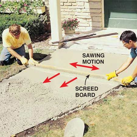 <b>Photo 11: Level and flatten with a screed board </b></br> Level concrete as you pour with a screed board (a straight 2x4 about 1 ft. longer than the width of the sidewalk). Rest the screed board on the forms and use a sawing motion while pulling the board toward the end of the pour. Fill lower areas with fresh concrete and repeat screeding over the same area.