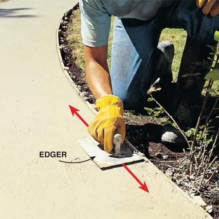 <b>Photo 14: Round over edges </b></br> Round over the outside corners with an edging tool. Use a back-and-forth motion in a 1- to 2-ft. area, lifting the leading edge on each pass and working your way down the sidewalk edge.