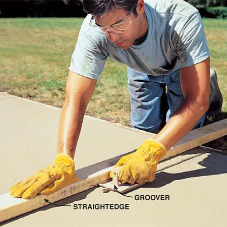 <b>Photo 15: Cut control joints </b></br> Cut in control joints every 5 to 6 ft. with a groover. Plan your cuts by measuring the length of the pour and evenly dividing it so all the segments are about the same length. During the first pass, use a straight board held perpendicular to the forms for guiding the groover.