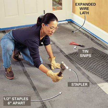 <b>Photo 3: Staple down metal lathe</b></br> Cut sheets of Expanded metal lath with a tin snips to fit around obstacles and between walls. Allow each piece to lap over the previous one about 2 in. Secure the lath to the floor with 1/2-in. staples placed about 6 in. apart. Staple from the center of the sheet to the outside to eliminate bulges.