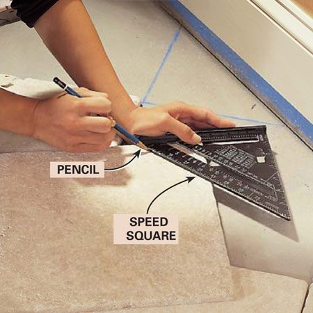 <b>Photo 9: Mark the tiles</b></br> Measure and mark the tile. Then make a diagonal cutting line across the mark with a Speed square. Number the tiles on the back so you can precut and position them correctly when you're ready to install it.