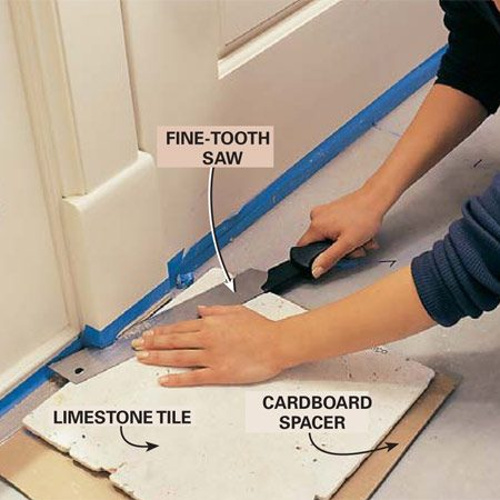 <b>Photo 11: Undercut door trim</b></br> Saw off the bottom of door trim or door jambs so the tile will slide under them. Set a floor tile on a piece of cardboard to guide the saw cut. Use a saw with sharp, fine teeth. Remove the cutoff chunk of molding with a screwdriver or small chisel.