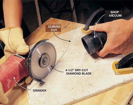 <b>Photo 13: Cut the curves</b></br> Make curved cuts using a dry-cut diamond blade mounted in a 4- or 4-1/2 in. grinder. Firmly clamp the tile to a piece of plywood laid over sawhorses. Wearing a dust mask, hearing protection and safety goggles, score along the line with the diamond blade. Use a shop vacuum to collect the dust and chips. Make three or four passes with the grinder to gradually saw through the tile. Round over the cut edge of the tile with 80-grit sandpaper.