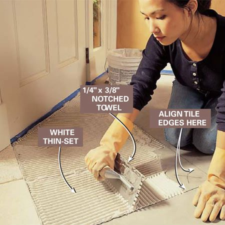 <b>Photo 14: Spread thin-set mortar</b></br> Mix thin-set mortar according to the instructions on the package to the consistency of peanut butter. Trowel a layer of thin-set up to your layout lines, covering about 6 or 8 sq. ft. Press the thin-set onto the mortar bed to form a good bond. Go over the entire area with the notched trowel held at 45 degrees to the floor to create an even layer of ridged thin-set.