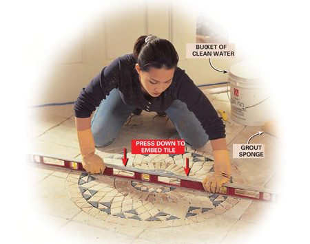 <b>Photo 17: Flatten the medallion</b></br> Press the medallion into the thin-set to embed it and bring it flush to the surrounding tile. Use a straight board or level to tamp over the entire area. If you need to raise or lower pieces or sections of the medallion, cut through the mesh backing with a utility knife before lifting them out. Then add or remove thin-set to bring the pieces to the proper level.