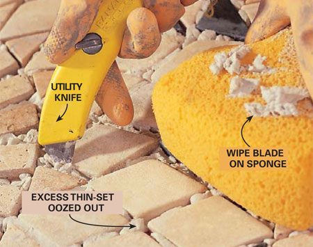 <b>Photo 18: Clean between tiles</b></br> Scrape the excess thin-set from between the pieces of marble with the point of a utility knife. Use a sponge to collect excess thin-set and clean the face of the tiles as you go. Allow the thin-set to harden overnight.