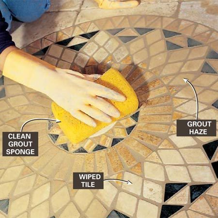 "<b>Photo 21: Clean the surface</b></br> Clean the grout film from the face of the tile with a special grout sponge. Allow the grout to ""firm up"" in the joint before cleanup. Do not allow the grout film to harden or dry on the face of the tile. It will be very difficult to remove. Start by scrubbing the face of the tile with a wrung-out sponge, rinsing the sponge in clean water when it fills with grout. Complete the cleanup process by making long overlapping swipes, using a clean face of the sponge for each pass. Polish the tile with a soft cloth to remove dried grout haze."