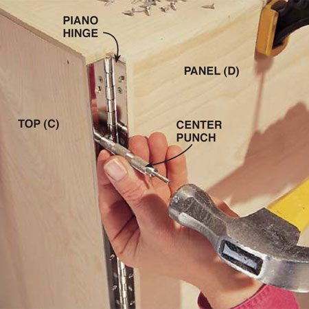 <b>Photo 6: Fasten the piano hinges</b></br> Tip the bench onto its side. Align each tip-up panel (D) with the bench frame so your 1-1/2 in. piano hinge fits as shown. Align your screw holes perfectly with a center punch or a Vix bit.