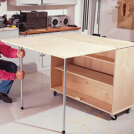 <b>Photo 8: Open the bench and thread on the legs</b></br> Twist the 3/4-in. threaded pipe onto the pipe flanges for a rock-solid workbench. Be sure to lock the casters in place when using the bench.