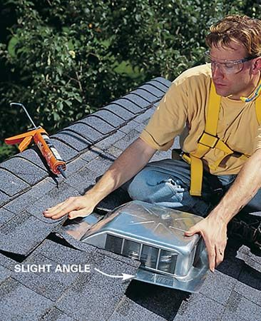 <b>Photo 12: Push the vent under the shingles</b></br> Hold the vent up at an angle and slide it into place. Then set it down into the roofing cement.