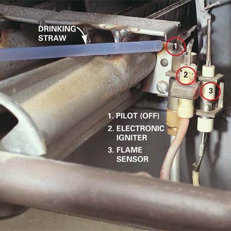 <b>Photo 7: Clean the pilot</b></br> <p>Blow  dust off the pilot. Direct air to the exact spot by blowing through a drinking  straw. A dirty pilot can cause the flame sensor (or thermocouple) to get a  false reading that the pilot isn't lit. Some newer furnaces have hot surface  igniters instead of pilots and electronic igniters (Photo 9). (Note: One burner  was removed for clarity.) </p>