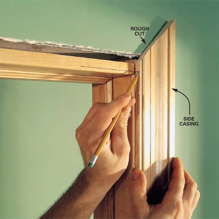 <b>Photo 4: Cut the side casing</b></br> Cut the side casing about 1/2 in. overlong and hold it in place on the door jamb along your reveal marks. Use a sharp pencil to transfer the top reveal mark from the head jamb to the side casing. Then cut the miter at the angle you established with your test pieces.