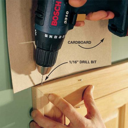 <b>Photo 8: Predrill the corners</b></br> Align the miters and predrill a 1/16-in. hole for 3d finish nails, one from the top and one from the side. Hold a piece of cardboard against the wall to prevent marring the wall while drilling.