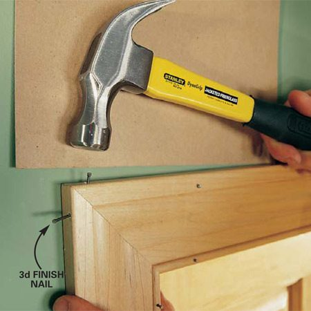 <b>Photo 9: Nail the corners</b></br> Drive the nails into the casing gradually, alternating between the two nails so the miter doesn't slide out of alignment. Use cardboard again between the wall and the hammer to avoid marring the wall.