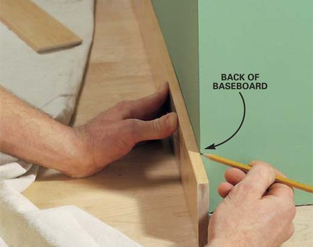 <b>Photo 15: Cut miter to length</b></br> Hold the baseboard in place and mark the backside at the corner. Now cut the piece to length at the predetermined angle for an exact fit.