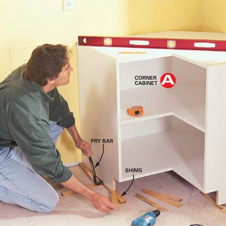 <b>Photo 4: Get an accurate start </b></br> Set and level the corner cabinet first. Shim the cabinet to the horizontal level lines you marked on the wall. Be fussy, since all the other cabinets attach to this cabinet. Make any adjustments to out-of-plumb walls at this point (see text).