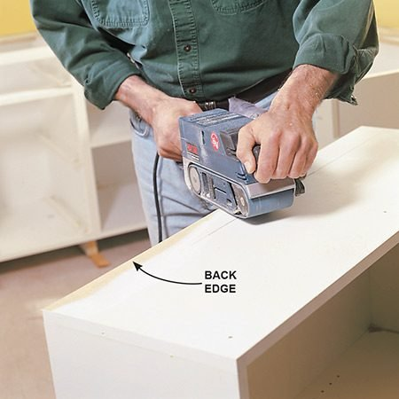 <b>Photo 9: Adapt the corner, if necessary </b></br> Sand the back edge of the corner cabinet if the drywall mud is thick and holds the cabinet out from the corner. Sand back a couple of inches from the back and fit it again.
