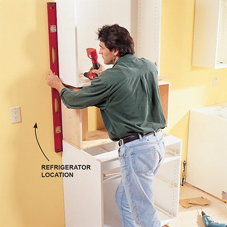 <b>Photo 10: Use a level for alignment </b></br> Align the wall cabinets exactly with the base cabinets where critical appliance placements are necessary. Here the refrigerator end panel (K1) must be fastened to the wall and base cabinets. On the right side, the range and hood tuck in between the wall and the base cabinets.