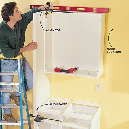 <b>Photo 11:  Use clamps to draw cabinets together </b></br> Scribe the refrigerator end panel to the floor if necessary, then precisely align and clamp the panel to the wall and base cabinets. Drill pilot holes and then screw the panel to the cabinets using the screw and sleeve fasteners or 1-1/4-in. screws. Fasten the bottom of the panels to the floor with steel angle brackets a few inches back from the front face (they'll be concealed once the fridge is in place).